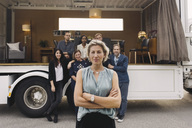 Portrait of confident businesswoman with team and portable office truck in background - MASF02224