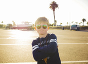 Portrait of confident boy wearing sunglasses while standing arms crossed at parking lot on sunny day - MASF02233