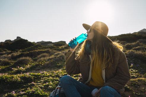 Italy, Sardinia, woman on a hiking trip having a break drinking from water bottle - KKAF00936