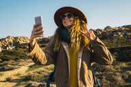 Italy, Sardinia, happy woman on a hiking trip taking a selfie - KKAF00942