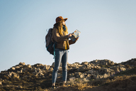 Italy, Sardinia, woman holding map on a hiking trip - KKAF00945