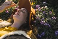 Woman lying in meadow enjoying fragrance of a flower - KKAF00951