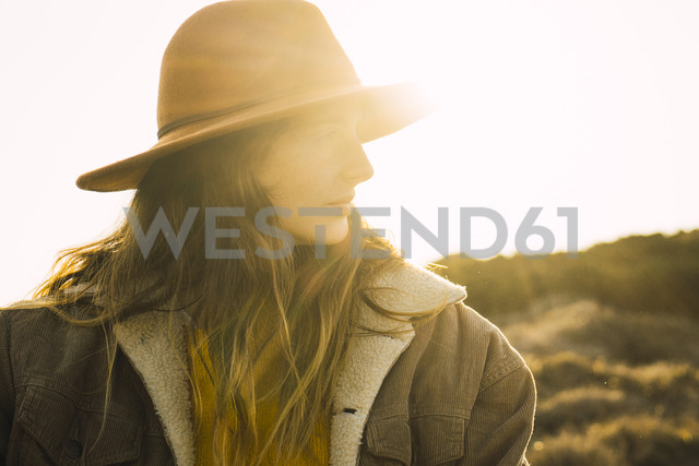 Italy, Sardinia, portrait of woman on a hiking trip at sunset - KKAF00954