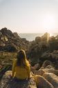 Italy, Sardinia, woman on a hiking trip sitting on rock at the coast - KKAF00957