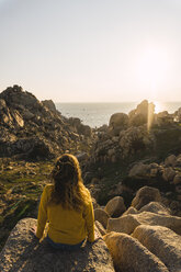 Italy, Sardinia, woman on a hiking trip sitting on rock at the coast - KKAF00957