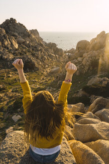 Italy, Sardinia, woman on a hiking trip sitting on rock at the coast raising her arms - KKAF00960
