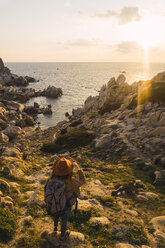 Italy, Sardinia, woman on a hiking trip standing on rock at the coast - KKAF00963