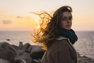 Italy, Sardinia, portrait of woman at the coast at sunset - KKAF00969