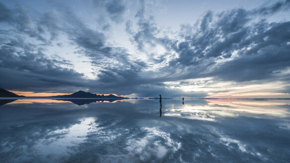 Silhouette people standing on Bonneville Salt Flats against cloudy sky - CAVF35578