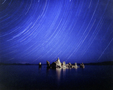 Scenic view of rock formations in Mono lake against star trails at night - CAVF35653