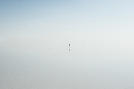 High angle view of woman standing in lake against sky during foggy weather - CAVF35695