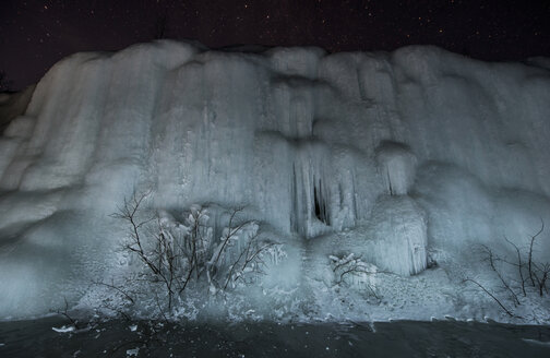 Low angle view of frozen waterfall during night - CAVF35707