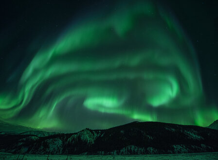 Majestic view of mountains against aurora borealis at Northern Rocky Mountains Provincial Park - CAVF35716