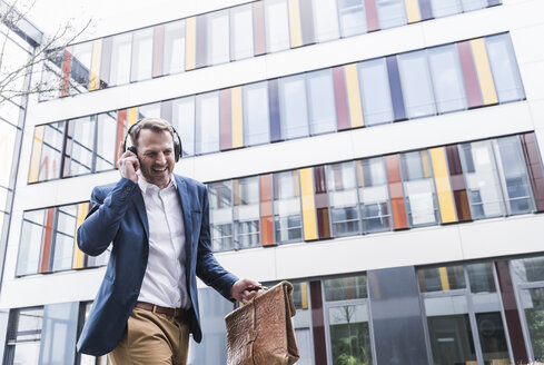 Happy businessman listening to music with headphones - UUF13271
