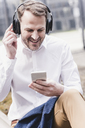 Smiling businessman with headphones and cell phone - UUF13274