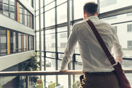 Rear view of businessman standing in office building leaning on railing - UUF13283