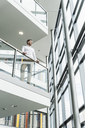 Businessman in office building leaning on railing - UUF13286