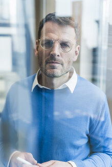 Focused businessman looking at glass pane - UUF13301