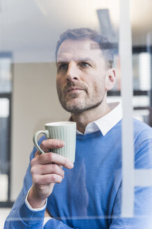 Focused businessman holding cup of coffee looking at glass pane - UUF13304