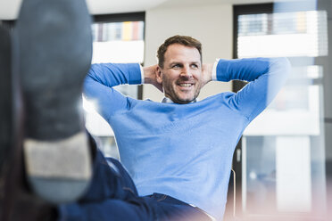 Smiling casual businessman in office leaning back - UUF13307