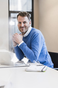 Portrait of smiling businessman with laptop in office - UUF13310