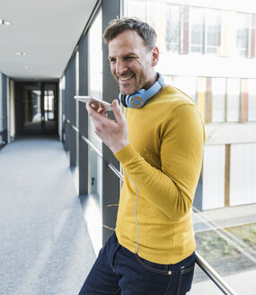 Casual smiling businessman in office using smartphone - UUF13313