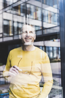 Happy casual businessman looking out of window - UUF13316