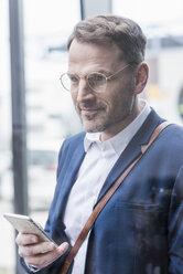 Portrait of confident businessman holding smartphone - UUF13319