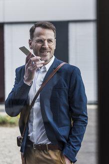 Smiling businessman using smartphone - UUF13322