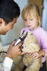 Doctor examining teddy bears ear at house call - CAVF35835