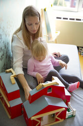High angle view of woman and daughter playing with model barn at home - CAVF35844
