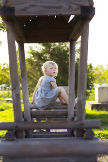 Portrait of girl sitting wooden structure at park - CAVF35847