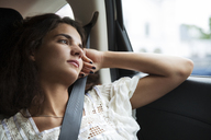 Thoughtful woman looking away while traveling in car - CAVF36003