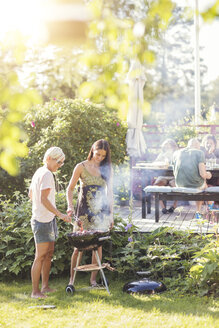 Mature women cooking food in barbecue at back yard during garden party - MASF02241