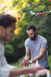 Men covering lit candles during garden party - MASF02250