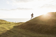 Mid distance of man jogging on grassy hill during sunny day - MASF02262