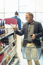Mature man reading label on food package in supermarket - MASF02277