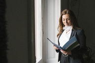 Mature female real estate agent reading brochure while standing by window at home - MASF02286