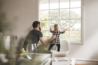 Mid adult man with daughter looking through window at home - MASF02298
