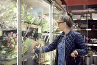 Mature woman buying flowers from glass cabinet at supermarket - MASF02307