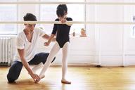 Male ballet teacher instructing ballerina in studio - CAVF36121