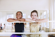 Portrait of cute ballerinas leaning on rod in studio - CAVF36139