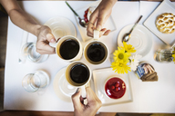 Cropped image of friends toasting with coffee cups at table in restaurant - CAVF36205