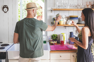 Man and woman arranging cups on shelf in kitchen at home - MASF02314