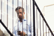 Low angle view of businessman using smart phone on steps at office yard - MASF02317
