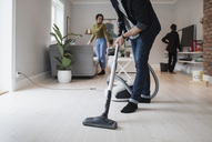 Low section of man vacuuming floor with woman and son in living room - MASF02323