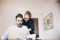 Low angle view of happy couple looking at laptop in domestic room - MASF02359