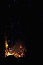 Man cooking food on campfire in forest at night - MASF02365