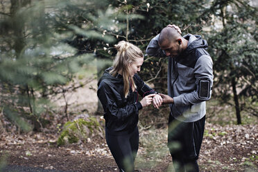 Male and female athletes checking smart watch in forest - MASF02368