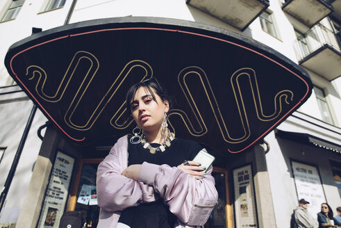 Low angle portrait of young woman standing at entrance of building in city - MASF02371